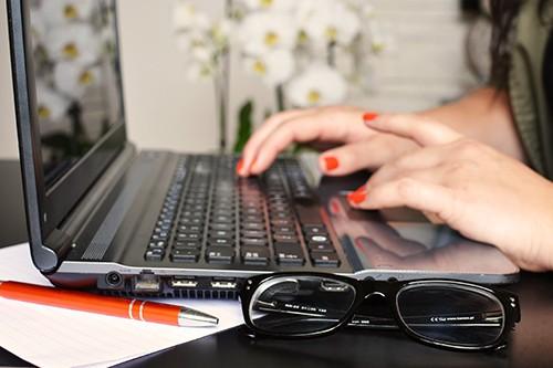 female using laptop on desk